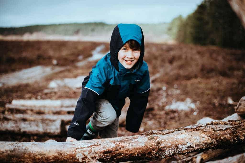 Junge spielt im Wald und schaut zu seinem Vater auf um zu zeigen, dass die Vereinbarkeit von Familie und Beruf als Vater dazu dient um Zeit mit den Kindern zu verbringen