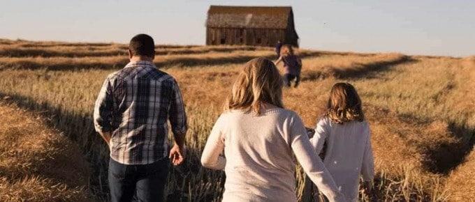 moderne Familie läuft durch ein Kornfeld