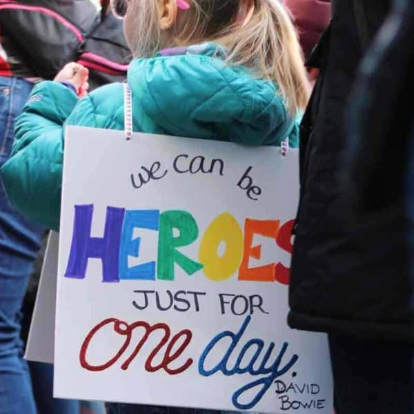 Kind trägt Schild auf dem rücken auf dem steht we can be heroes just for one da